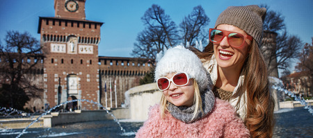 mam: Rediscovering things everybody love in Milan. Portrait of smiling modern mother and daughter travellers in sunglasses in Milan, Italy looking into the distance