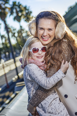 in Barcelona for a perfect winter. smiling modern mother and daughter tourists on embankment in Barcelona, Spain hugging