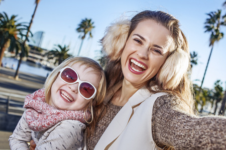 in Barcelona for a perfect winter. smiling young mother and daughter tourists on embankment in Barcelona, Spain taking selfie Stock Photo
