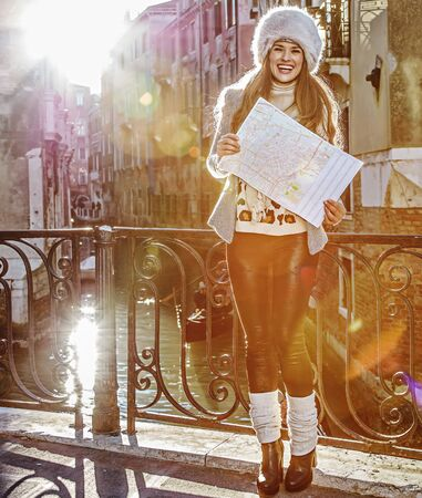 Venice. Off the Beaten Path. Full length portrait of happy young woman in fur hat in Venice, Italy in the winter with map