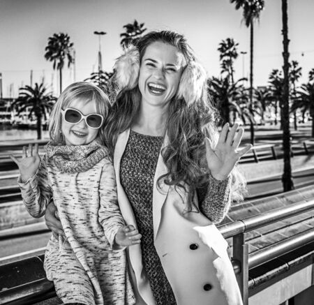 in Barcelona for a perfect winter. Portrait of smiling modern mother and daughter travellers in Barcelona, Spain handwaving