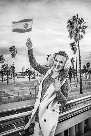 in Barcelona for a perfect winter. happy young fashion-monger in earmuffs in Barcelona, Spain rising flag Stock Photo