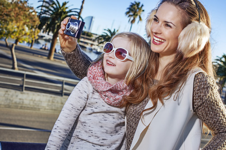 in Barcelona for a perfect winter. smiling young mother and child travellers in Barcelona, Spain with digital camera taking photo