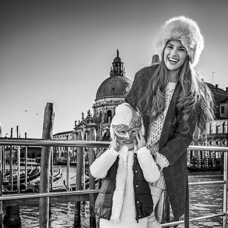 Another world vacation. Full length portrait of smiling trendy mother and child tourists on embankment in Venice, Italy wearing Venetian mask