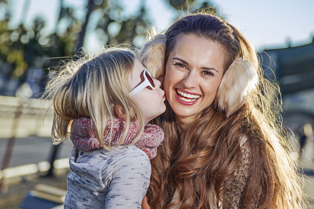 in Barcelona for a perfect winter. smiling young mother and child tourists in Barcelona, Spain kissing