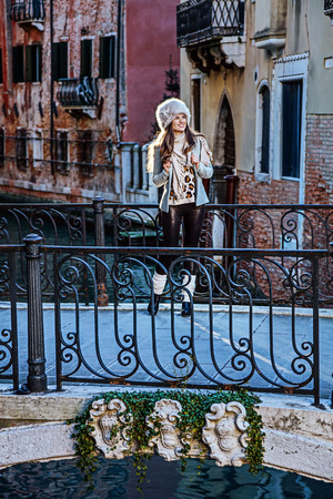 Venice. Off the Beaten Path. Full length portrait of smiling young traveller woman in fur hat in Venice, Italy in the winter looking into the distance