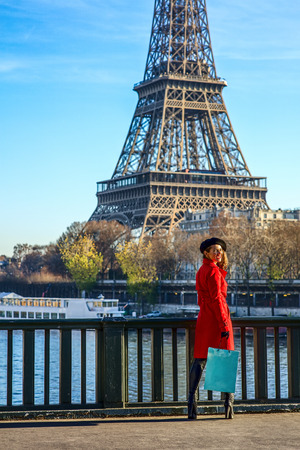 Bright in Paris. Full length portrait of happy trendy woman in red trench coat standing on embankment in Paris, France Stock Photo