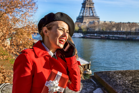 Bright in Paris. happy trendy woman in red trench coat on embankment in Paris, France using a cell phone and holding present box