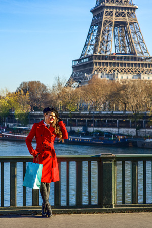 Bright in Paris. Full length portrait of smiling elegant woman in red trench coat standing on embankment near Eiffel tower in Paris, France