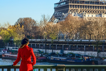 Bright in Paris. Seen from behind trendy woman in red trench coat standing on embankment near Eiffel tower in Paris, France