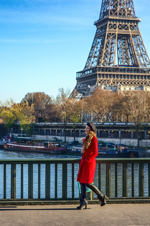 Bright in Paris. Full length portrait of smiling elegant woman in red trench coat on embankment in Paris, France walking Stock Photo