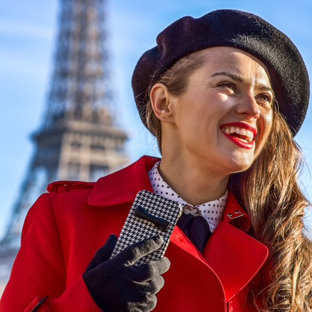 Bright in Paris. Portrait of smiling elegant woman in red trench coat on embankment near Eiffel tower in Paris, France with smartphone