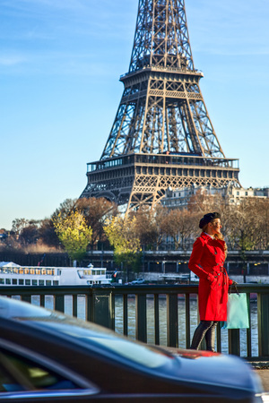 Bright in Paris. Full length portrait of elegant woman in red trench coat on embankment near Eiffel tower in Paris, France looking aside
