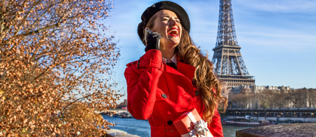 Bright in Paris. cheerful trendy woman in red trench coat on embankment in Paris, France using a cell phone and holding present box