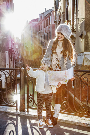 Venice. Off the Beaten Path. Full length portrait of happy young mother and child tourists in Venice, Italy in the winter with map