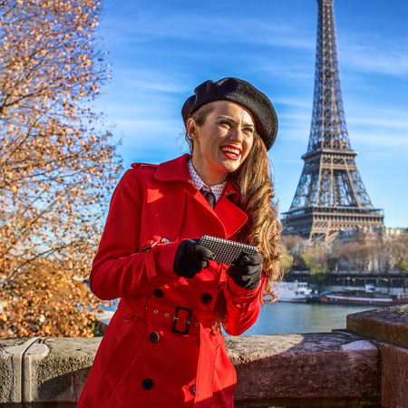 Bright in Paris. happy trendy woman in red trench coat on embankment in Paris, France writing sms