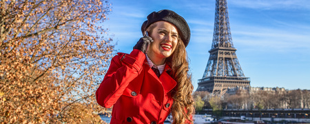 Bright in Paris. happy modern woman in red trench coat on embankment near Eiffel tower in Paris, France talking on a smartphone