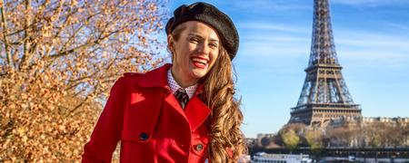 Bright in Paris. Portrait of happy young woman in red trench coat on embankment in Paris, France