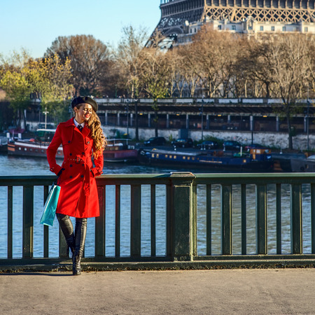 Bright in Paris. Full length portrait of relaxed elegant woman in red trench coat standing on embankment in Paris, France