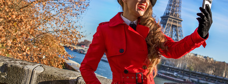 Bright in Paris. happy modern woman in red trench coat on embankment near Eiffel tower in Paris, France taking selfie Stock Photo