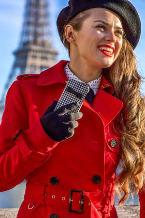 Bright in Paris. Portrait of happy elegant woman in red trench coat on embankment in Paris, France with smartphone
