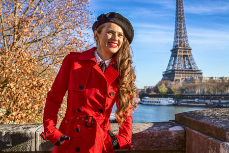 Bright in Paris. smiling modern woman in red trench coat on embankment near Eiffel tower in Paris, France looking into the distance
