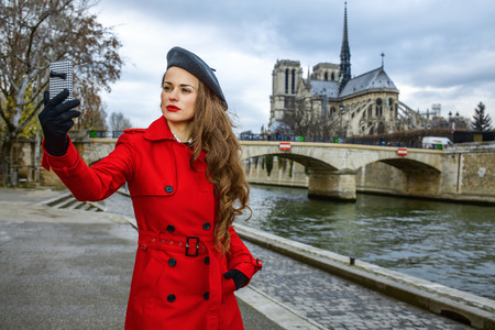 Bright in Paris. modern woman in red trench coat on embankment near Notre Dame de Paris in Paris, France with phone taking selfie Stock Photo