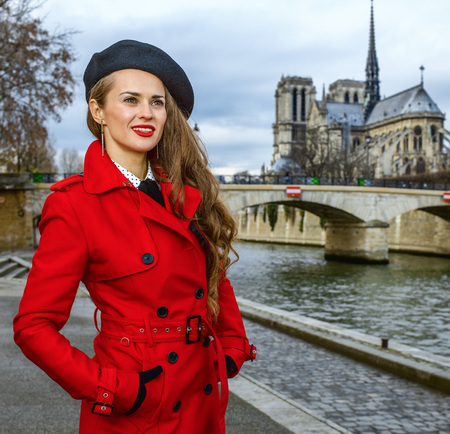 Bright in Paris. modern woman in red trench coat on embankment near Notre Dame de Paris in Paris, France looking into the distance