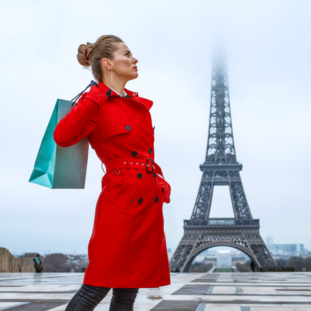 Bright in Paris. Full length portrait of trendy woman in red trench coat in the front of Eiffel tower in Paris, France with shopping bag Stock Photo