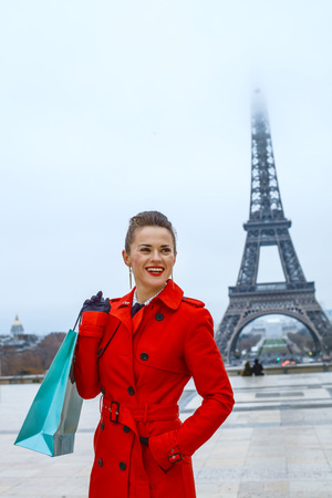 Bright in Paris. Portrait of smiling trendy woman in red trench coat in the front of Eiffel tower in Paris, France with shopping bag looking aside Stock fotó