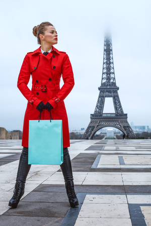 Bright in Paris. Full length portrait of modern woman in red trench coat against Eiffel tower in Paris, France with shopping bag looking aside Stock Photo