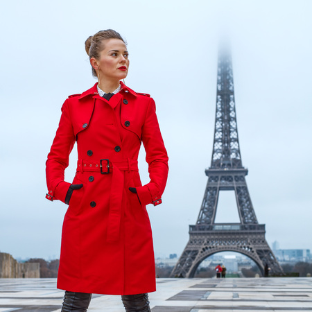 Bright in Paris. Full length portrait of young woman in red trench coat against Eiffel tower in Paris, France looking aside Stock Photo