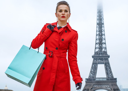 Bright in Paris. Full length portrait of stylish woman in red trench coat in Paris, France with shopping bag looking into the distance Stock Photo