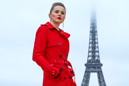 Bright in Paris. Full length portrait of young woman in red trench coat against Eiffel tower in Paris, France