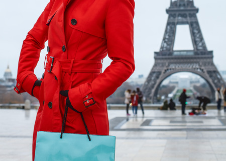 Bright in Paris. Closeup on modern woman in red trench coat against Eiffel tower in Paris, France with shopping bag looking into the distance Stock Photo