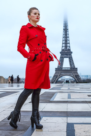 Bright in Paris. Full length portrait of young woman in red trench coat standing against Eiffel tower in Paris, France