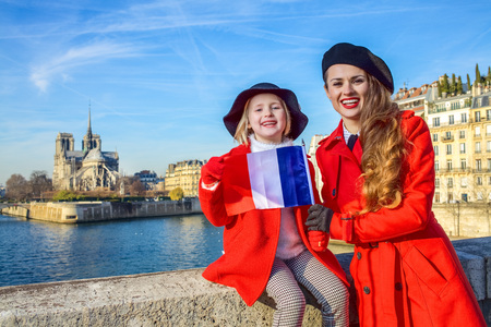 Bright in Paris. Portrait of modern mother and child tourists in red coats on embankment in Paris, France with French flag