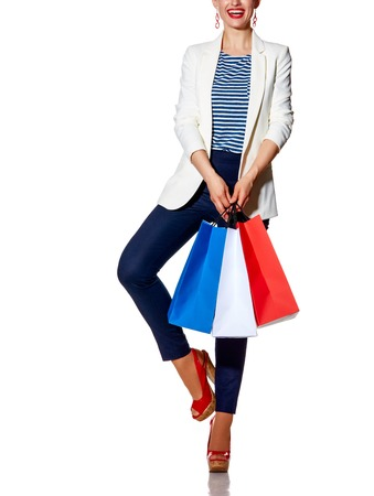 french way: Shopping. The French way. Closeup on happy young woman with French flag colours shopping bags posing against white background