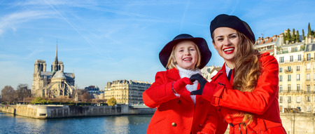 Bright in Paris. stylish mother and daughter travellers in red coats on embankment in Paris, France showing heart shaped hands