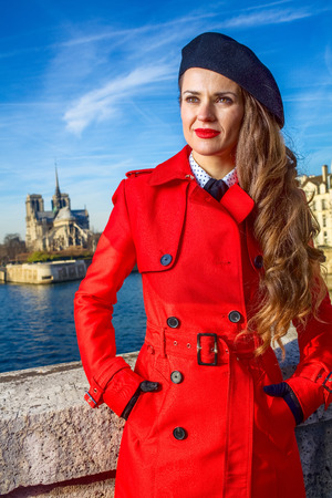 Bright in Paris. trendy traveller woman in red trench coat on embankment in Paris, France looking into the distance Stock Photo