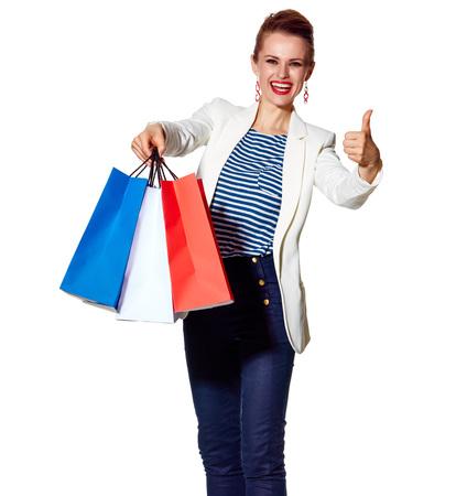 Einkaufen. Der französische Weg. Porträt in voller Länge der glücklichen jungen Frau, die französische Flagge zeigt, färbt Einkaufstaschen und greift oben auf weißem Hintergrund ab Standard-Bild - 74508024