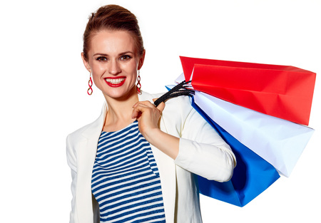 Shopping. The French way. Portrait of happy young woman with French flag colours shopping bags on white background
