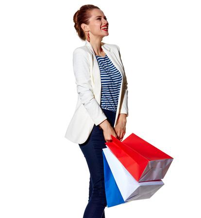 Einkaufen. Der französische Weg. Ganzaufnahme der aufgeregten jungen Frau mit französischer Flagge färbt Einkaufstaschen auf dem weißen Hintergrund, der beiseite schaut Standard-Bild - 74508276
