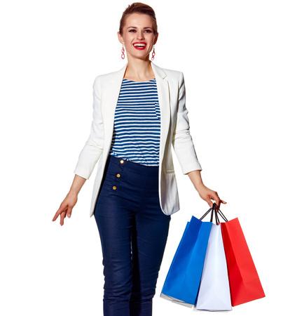 Einkaufen. Der französische Weg. Ganzaufnahme der glücklichen jungen Frau mit französischer Flagge färbt Einkaufstaschen auf dem weißen Hintergrund, der vorwärts geht Standard-Bild - 74508016