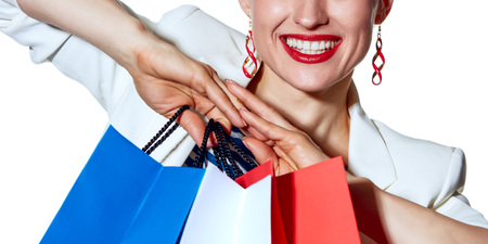 french way: Shopping. The French way. Close Closeup on happy young woman with French flag colours shopping bags on white background