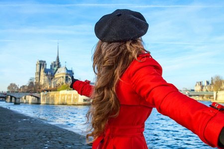 Bright in Paris. modern woman in red trench coat on embankment near Notre Dame de Paris in Paris, France holding friends hand and pointing at Notre Dame de Paris Stock Photo