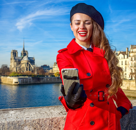 Bright in Paris. smiling stylish traveller woman in red trench coat on embankment near Notre Dame de Paris in Paris, France with phone taking selfie