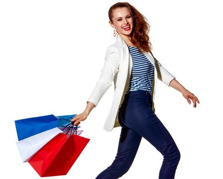 Einkaufen. Der französische Weg Ganzaufnahme der lächelnden jungen Frau, die mit französischer Flagge geht, färbt Einkaufstaschen auf weißem Hintergrund Standard-Bild - 74506825
