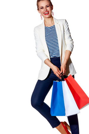 Shopping. The French way. happy young woman with French flag colours shopping bags posing against white background
