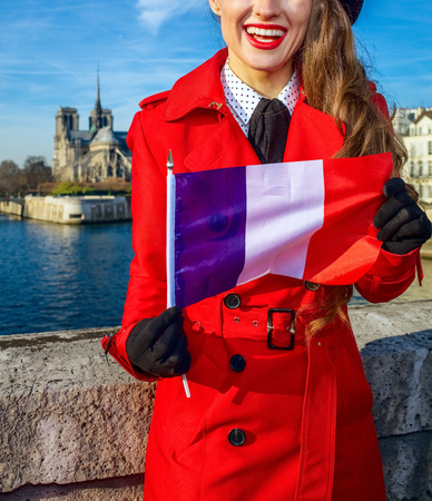 Bright in Paris. happy stylish woman in red trench coat on embankment near Notre Dame de Paris in Paris, France showing flag